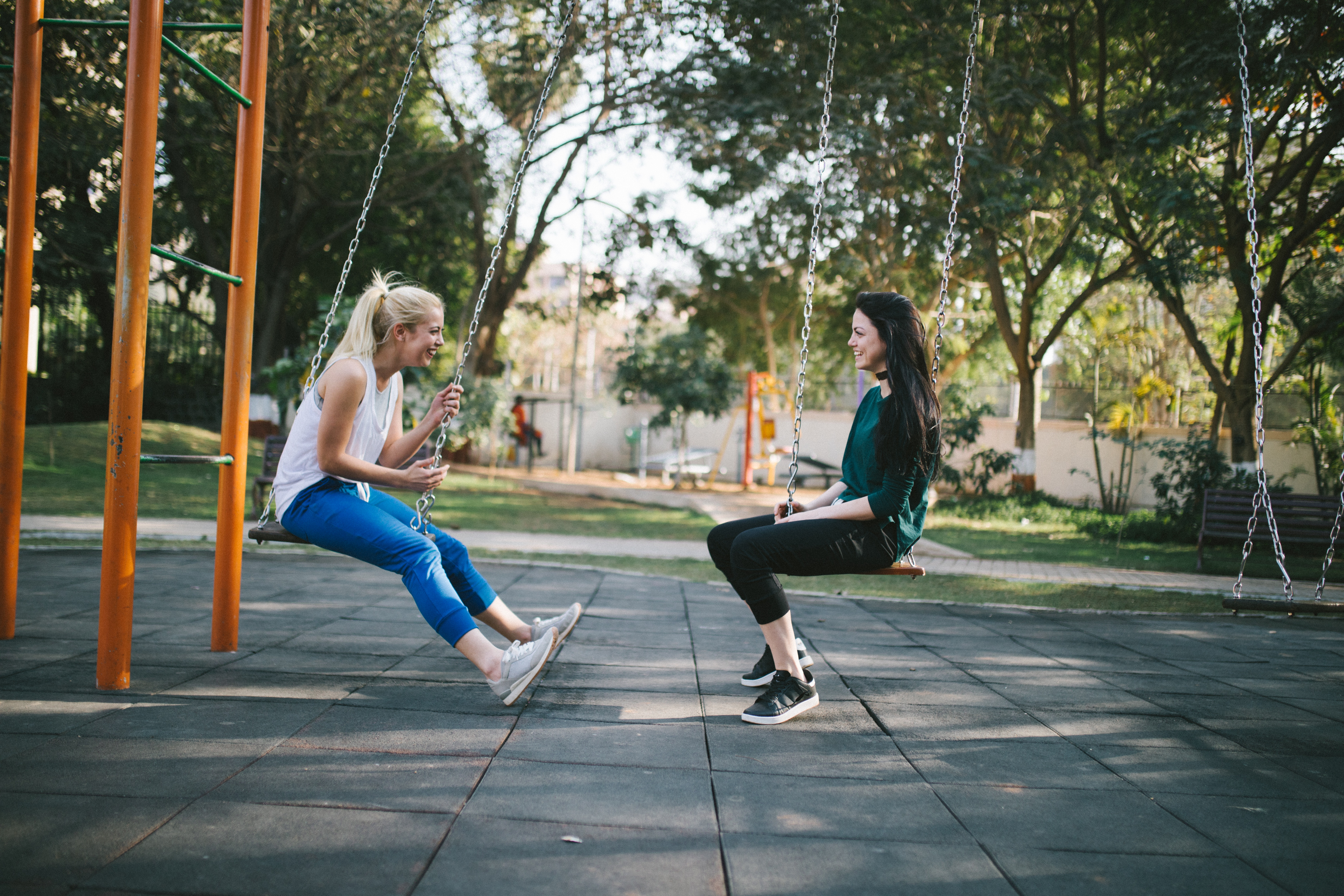 Two friends sitting on swings at a park, laughing and facing each other.