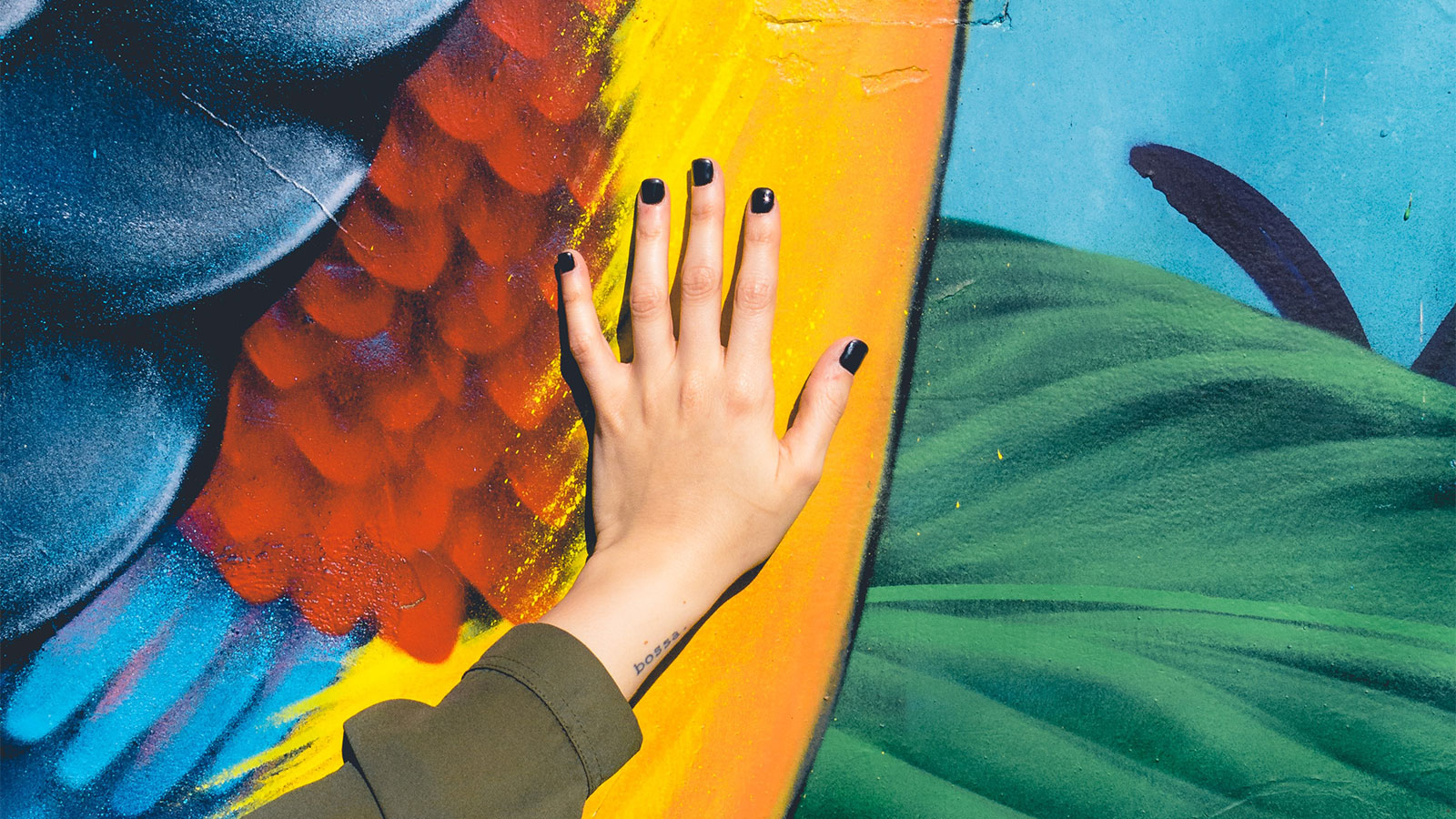 A hand with black painted nails laid flat over a brightly painted mural.