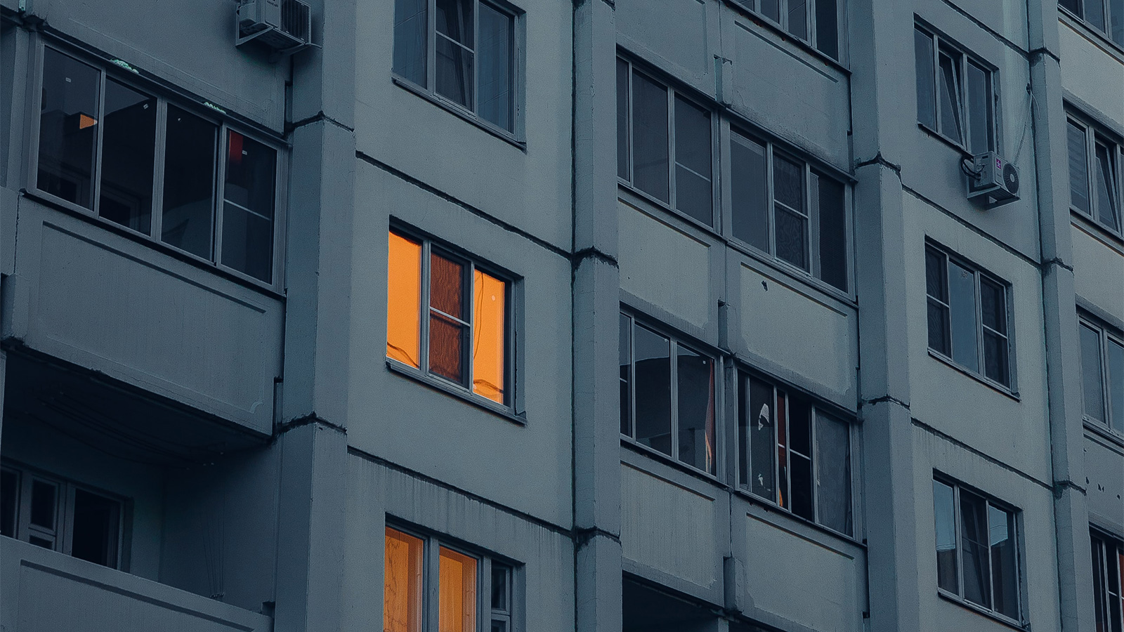 A window lit up in an apartment building at dusk.