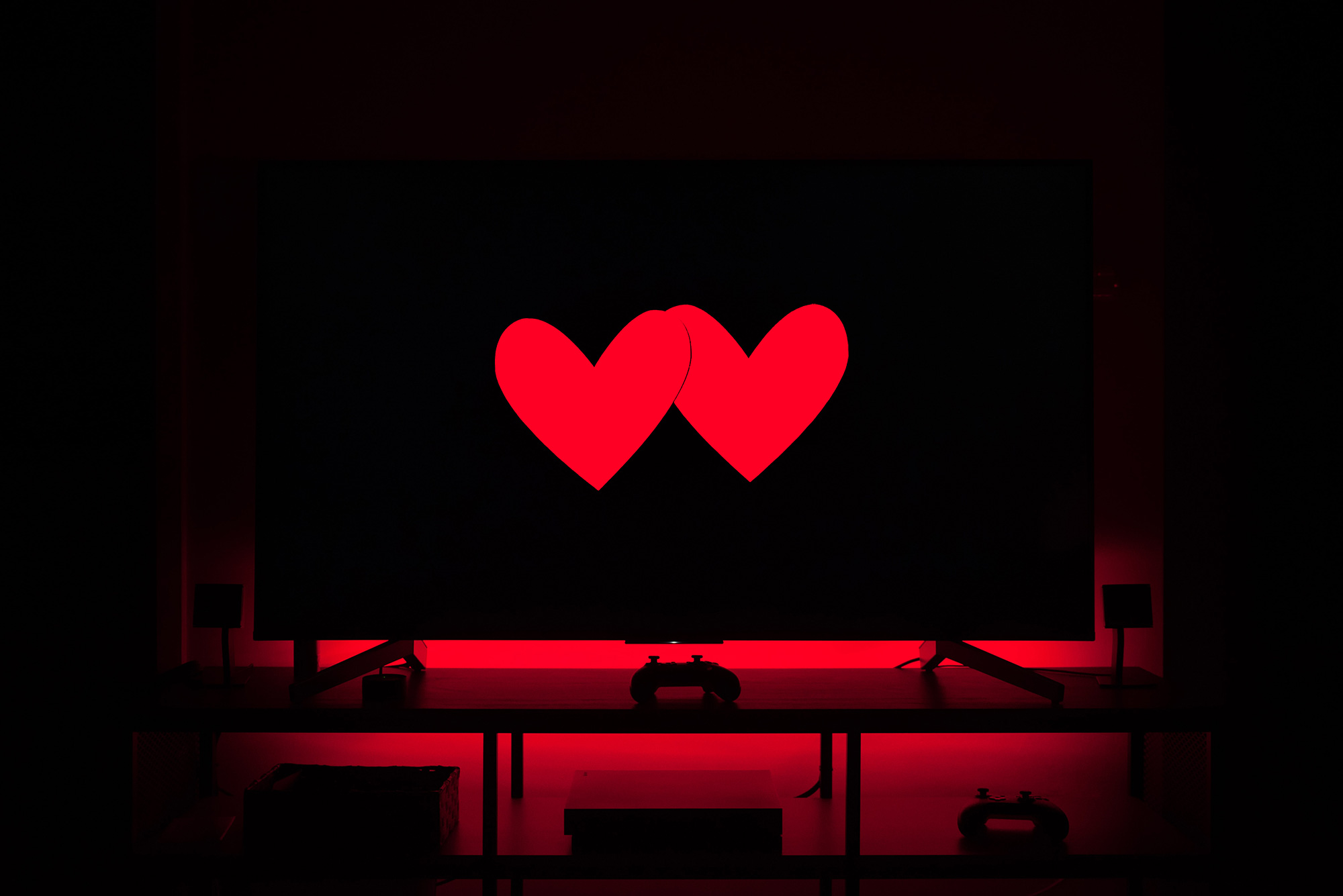 A television screen with two red paper hearts on it.