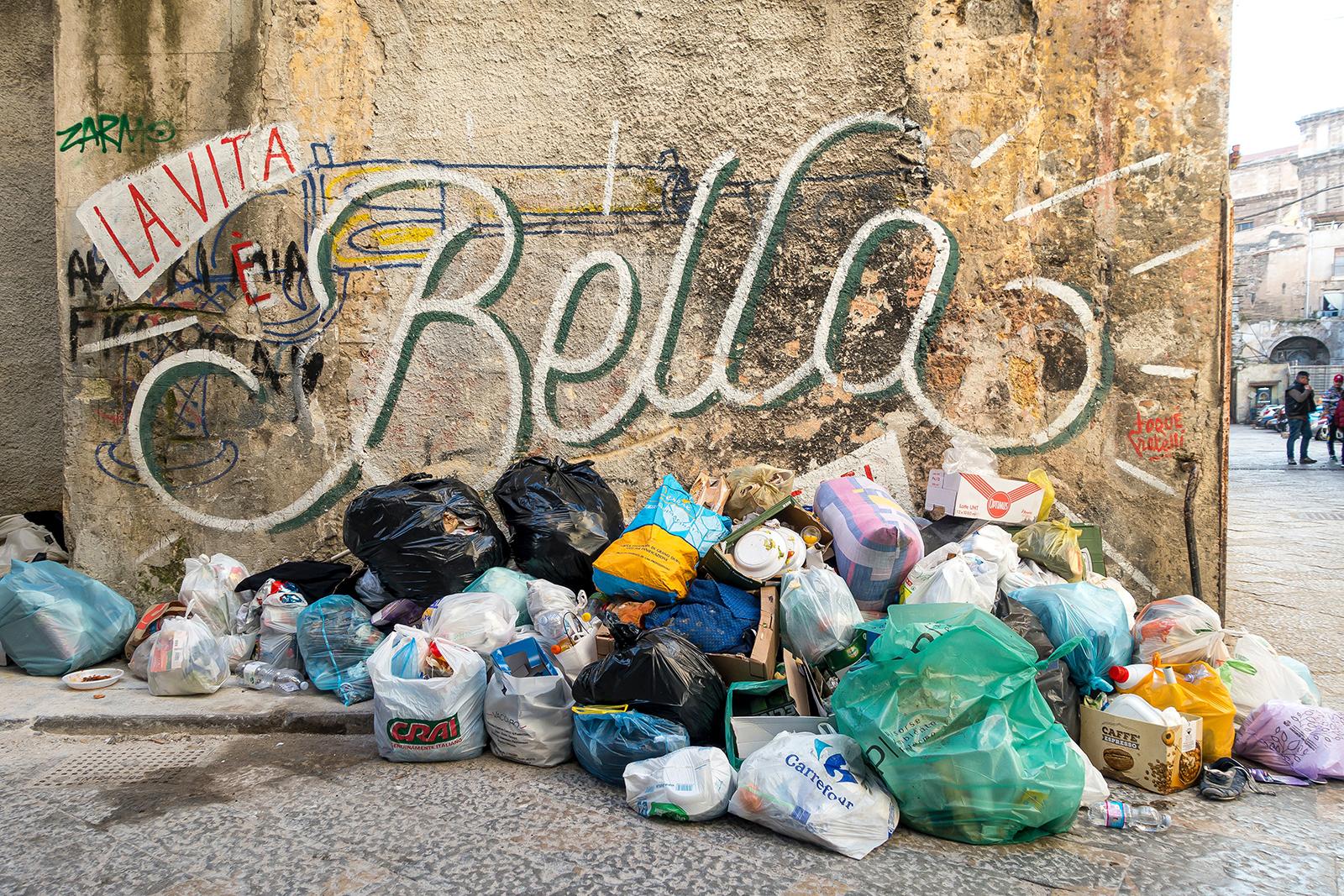 "A street corner featuring a ""La vita bella"" mural and a pile of trash bags."
