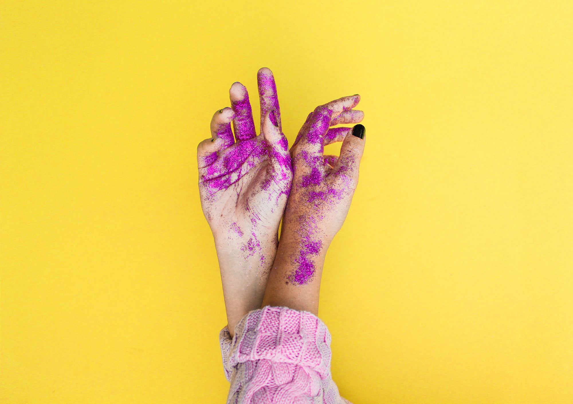 A pair of hands covered in purple glitter.
